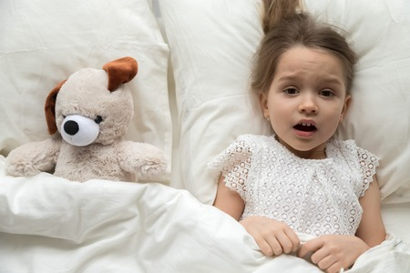 Scared frightened little kid girl looking at camera lying in bed on pillow with toy afraid of nightmare, terrified child awaking from bad dream sleep feeling fear disturbed by scary monster, top view
