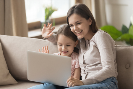 Happy family young mom with kid daughter looking at laptop screen waving hands make distance video call, smiling mother and little child girl talking to webcamera on internet chat by computer webcam Stok Fotoğraf