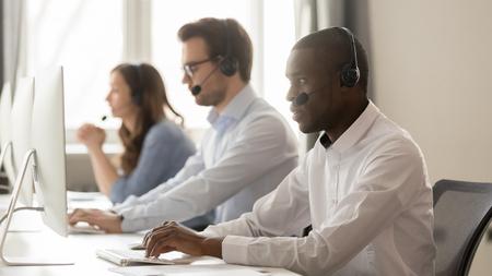 Ernstige Afrikaanse callcenteragent in draadloze headset die op computer werkt met divers team, gerichte zwarte mannelijke telemarketeer die pc gebruikt in het kantoor van de klantenservicegroep, helpdesk Stockfoto