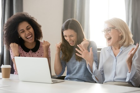 Diverse happy overjoyed young and old female employees team excited by online win reward business result, motivated businesswomen winners celebrate victory looking at laptop screen achieved new goal Banco de Imagens