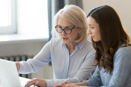 Ernstige oude vrouwelijke mentor leraar coach lesgeven stagiair of student computerwerk wijzend op laptop, volwassen uitvoerend manager die online project uitlegt aan jonge werknemer die nieuwe vaardigheden leert op kantoor