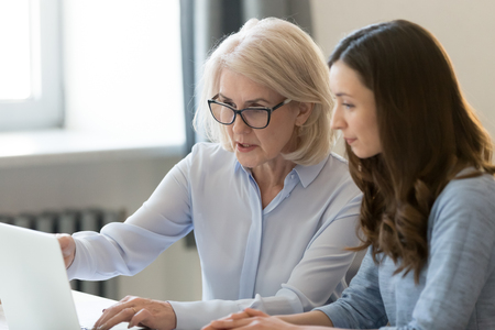 Serious old female mentor teacher coach teaching intern or student computer work pointing at laptop, mature executive manager explaining online project to young employee learning new skills in office 写真素材 - 119154623