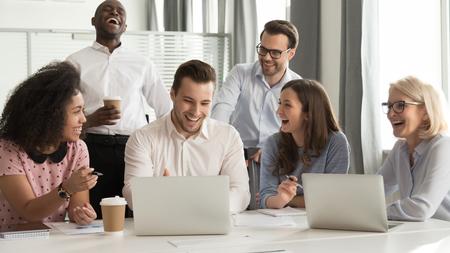 Felice allegro team di impiegati diversi che ride di uno scherzo divertente lavora insieme alla riunione di lavoro del gruppo aziendale, entusiasti dipendenti sorridenti colleghi che parlano divertendosi sul posto di lavoro con il laptop