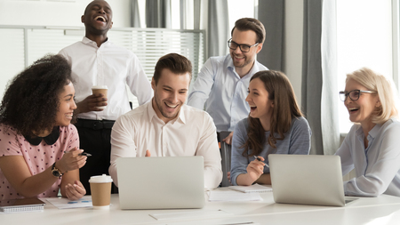 Happy cheerful diverse office workers team laughing at funny joke work together at corporate group business meeting, excited smiling employees colleagues talking having fun in workplace with laptop