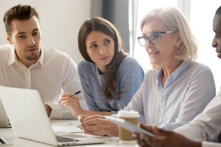 Fokussierte junge Studenten Praktikanten Arbeiter, die Notizen machen, die alten weiblichen Managern im Alter von Managern zuhören, die bei der Gruppenbürositzung sprechen und das Geschäftsteam mit Laptop anweisen.