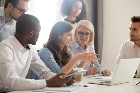 Entrenador de líder mentor femenino joven que enseña al grupo de empleados que analiza el proyecto en línea que explica la estrategia de negocio que habla entrenando diverso equipo corporativo con la computadora portátil que usa la computadora en la reunión de la oficina.