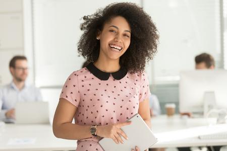 Felice fiducioso afroamericano donna d'affari dipendente in possesso di tablet digitale guardando la telecamera in piedi in ufficio, sorridente millenario razza mista stagista manager giovane ritratto professionale