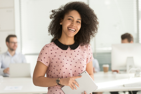 Happy confident african american business woman employee holding digital tablet looking at camera standing in office, smiling millennial mixed race female intern manager young professional portrait 免版税图像
