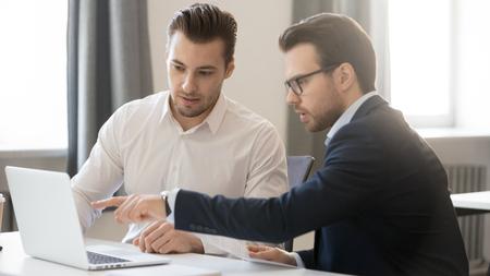 Hombre de negocios serio apuntando a la computadora portátil discutiendo el software corporativo con un colega en la oficina, el equipo ejecutivo masculino que trabaja en conjunto usa la computadora, el mentor gerente que consulta instruye al compañero de trabajo del cliente