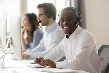 Happy african businessman call center agent in headset looking at camera at workplace, smiling black male telemarketer operator works on computer in customer support service helpdesk office, portrait 免版税图像