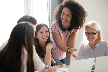 Positive friendly african and caucasian creative team employees talking laughing at company meeting, happy cheerful diverse workers group having fun involved in corporate office funny teambuilding Stock Photo