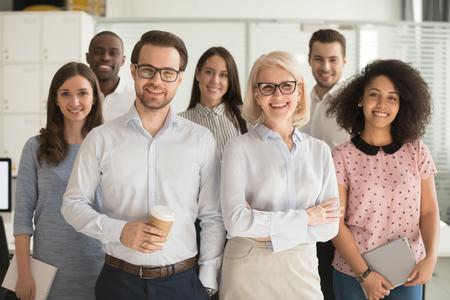Sonriendo a los mentores de líderes de entrenadores profesionales de negocios posando junto con el grupo de pasantes de diversos trabajadores de oficina, personal multicultural feliz empleados corporativos personas mirando a cámara, retrato de equipo