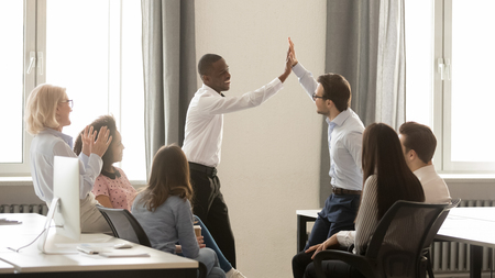 Happy diverse male employees winners giving high five together celebrating shared win, reward or great teamwork results, motivated by corporate success and good team relations at group office meeting