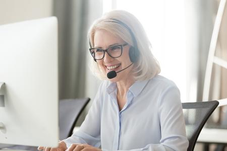Feliz vieja mujer de negocios en auriculares hablando por conferencia telefónica mirando la computadora, agente de centro de llamadas de mujer madura, operador de telemarketing hablando, consultoría, servicio al cliente, soporte en la oficina