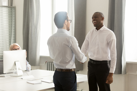 Happy african american male employee getting rewarded appreciated promoted by boss manager motivate praise acknowledge shake successful black office worker hand as gratitude loyalty respect concept.