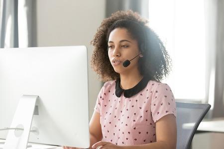 Jeune opérateur de centre d'appels africain sérieux, responsable de l'assistance à la clientèle dans un casque sans fil parlant à l'aide d'un ordinateur, femme de vente de télévendeurs de race mixte consultant le service d'assistance du service client au bureau