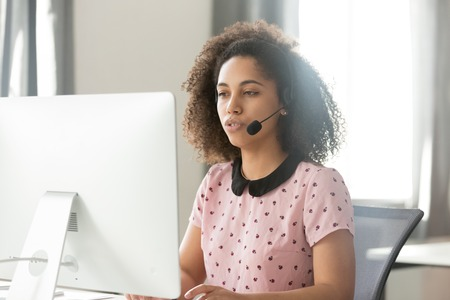 Serious young african call center operator customer care support manager in wireless headset talking using computer, mixed race telemarketer sales woman consulting client service helpdesk in office