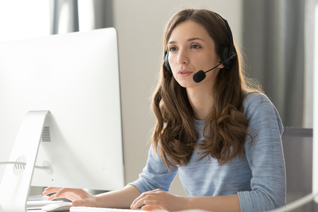Serious young businesswoman in wireless headset call center agent telemarketer consulting client participating business video conference talk help as customer care service support helpline in office.