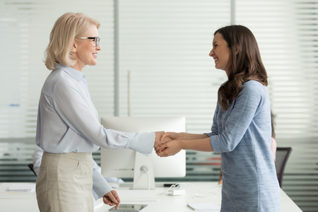 Happy young girl intern student worker get appreciated promoted hired rewarded handshaking helpful female old boss teacher, businesswomen handshake in office as gratitude recognition thanks concept 版權商用圖片