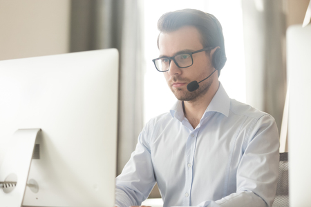 Serious businessman manager talking with headset on computer making business conference video call, focused technical support agent consulting client online working in customer care service office