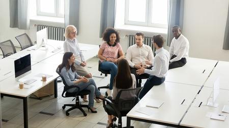 Männlicher Manager-Coach-Mentor, der beim Geschäftstreffen der Unternehmensgruppe spricht, Teamleiter im Gespräch mit Arbeitern, die Praktikanten im Workshop ausbilden und die neue Projektstrategie im Büro erklären, Draufsicht oben overhead