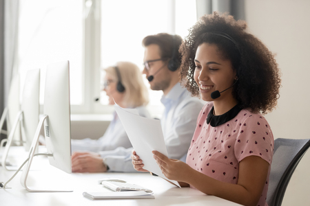 Smiling african american businesswoman call center operator agent wearing headset holding papers reading clients contacts working in customer service support helpdesk business office with colleagues.