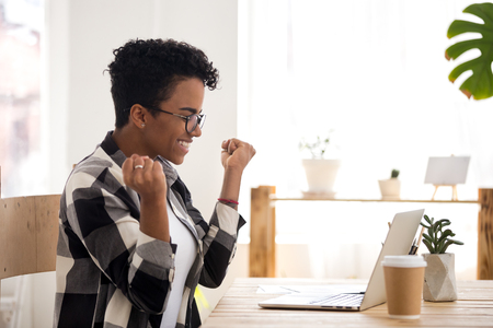 Happy black girl sitting at the desk looking at laptop. Excited woman feels happy received a scholarship, took on a good post or getting reward. Positive emotions showing gesture Yes I did it concept Banco de Imagens