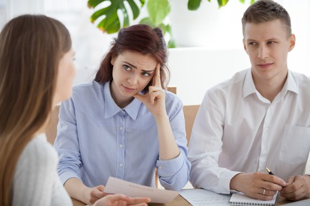 Serious HR managers advisors interviewing young woman student in the office. Employers holding curriculum vitae and looking at applicant girl with disbelief dissatisfied, bad first impression concept
