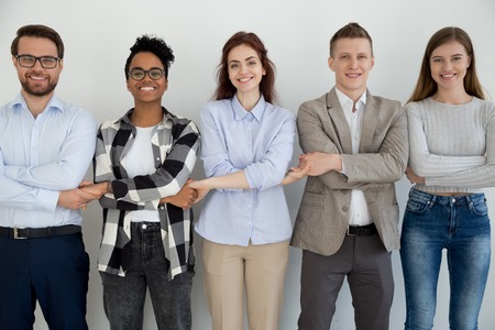Five cheerful diverse multiracial millennial businesspeople students holding hands standing opposite wall smiling and looking at camera. Team building unity support teamwork or common goal concept