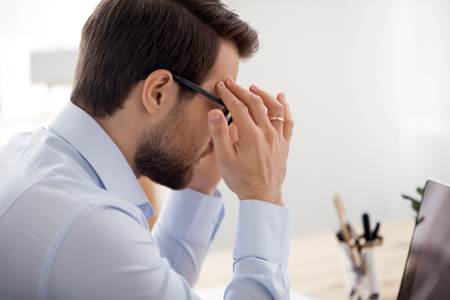 Stressed businessman with eyewglasses touching head working at office. Worker feels eyes fatigue and headache close up view over the shoulder. Influence of computer on human health overworking concept