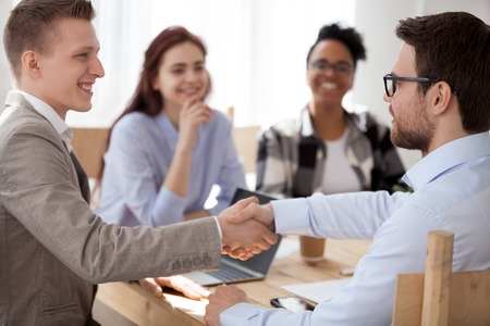 Diverse businesspeople sitting in office, happy businessmen shaking hands. Broker and client handshaking after sales negotiations, greeting, signing contract, HR recruitment reward or promote concept