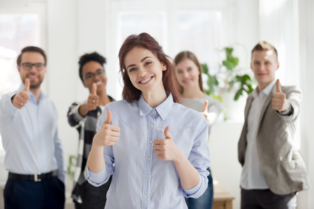 Happy girl with group of multiracial millennial positive businesspeople on background standing smiling together in office with thumbs up looking at camera. Teamwork collaboration and approval concept