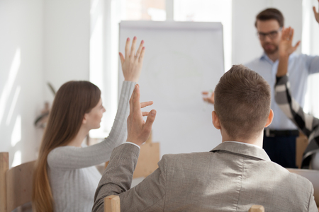 Group millennial businesspeople and ceo company during seminar in boardroom in office. Positive men and women raising hands symbol of agreement and unity concept, close up focus on participant back