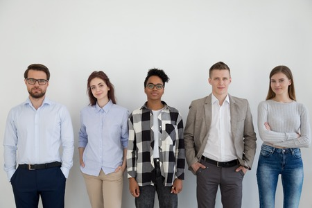 Young confident positive multiracial company staff professionals standing together opposite wall looking at camera. Diverse group business people employees posing in the office successful team concept