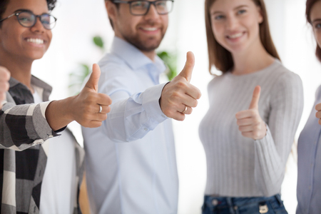 Happy multiracial millennial diverse business people or students standing together in a row smiling showing thumbs up, close up focus on hands. Successful teamwork collaboration and approval concept Stock Photo