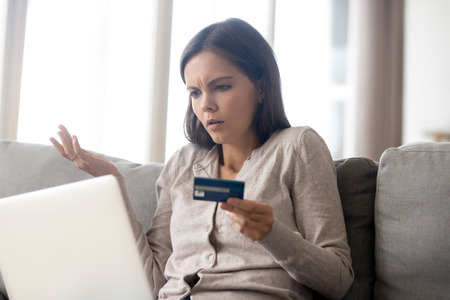Confused woman sitting on couch holds credit card use laptop looking at device screen having debt problems, transaction failed, money withdraw impossible, insecure online payment or scam fraud concept