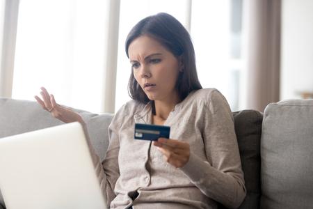 Zdezorientowana kobieta siedząca na kanapie trzyma laptop z kartą kredytową patrząc na ekran urządzenia mający problemy z zadłużeniem, transakcja nie powiodła się, wypłata pieniędzy jest niemożliwa, niepewna płatność online lub koncepcja oszustwa