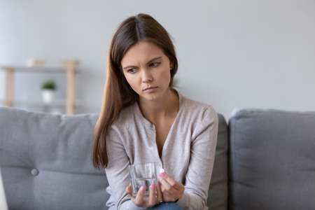 Lonely sad young woman sitting on sofa at home holding pill glass of water, concept of suicidal mood, feels unwell, pain relief, antidepressant emergency medicine, unwanted pregnancy abortion decision Standard-Bild