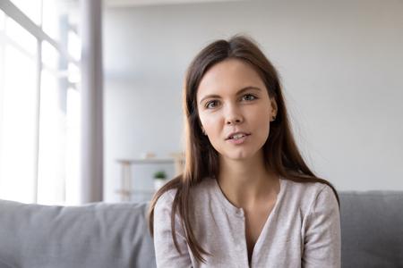 Kopfschuss Porträt junge Frau sitzt auf der Couch und schaut in die Kamera, die sich mit der modernen Computer-Webcam-Technologie unterhält, die mit einem Freund spricht, Mädchen, das Vlog aufzeichnet, das ein Vorstellungsgespräch aus der Ferne führt