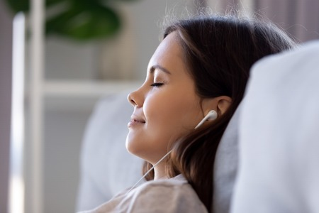 Close up profile view female closed eyes leaned on couch wearing earphones listening music, do meditation visualization dreaming feels happy good. Lazy weekend leisure activities serene person concept