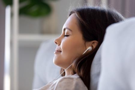 Vista ravvicinata del profilo occhi chiusi femminili appoggiati al divano indossando gli auricolari ascoltando musica, facendo la visualizzazione della meditazione sognando si sente felicemente bene. Concetto di persona serena attività ricreative del fine settimana pigro