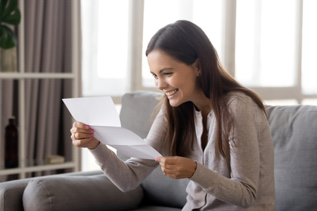 Excited young woman sitting on sofa holding reading letter with good news feels happy, received info from bank about loan approval or college admission scholarship, hired getting job of dream concept 스톡 콘텐츠