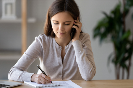 Pretty focused businesswoman sitting at desk holding cellular talking with client holding pen note on notepad complaints important information, girl distracted from study chatting with friend concept