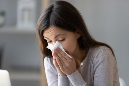 Sick young woman sitting indoors holding tissue handkerchief blowing running nose feels unwell unhealthy, girl having symptoms of chronic sinusitis disease, seasonal allergy or cold fever flu concept 写真素材