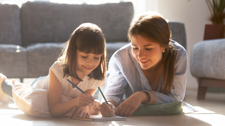 Mother and small adorable daughter lying in living room on warm floor holding colored pencils drawing on album paper notepad, loving mom helping teaching kid, leisure activities development concept