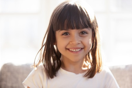 Head shot portrait happy cheerful pre-schooler girl sitting on couch in sunny room feels overjoyed healthy. Childcare, International Day of the Child, dental medicine for kids, beauty and love concept