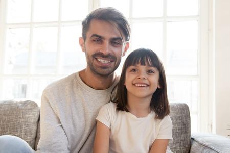 Niño feliz papá en casa, padre sentado en el sofá con hija pequeña sonriendo mirando a cámara, uso de cámara web portátil, hacer videollamadas, grabar un nuevo vlog familiar. Concepto en línea de tecnología y comunicaciones modernas