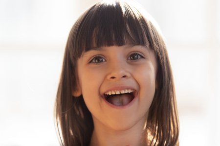 Close up portrait funny little happy preschool girl open mouth cheerful happy and overjoyed facial expressions. Adorable daughter kid face healthy child, carefree childhood, innocence beauty concept Standard-Bild