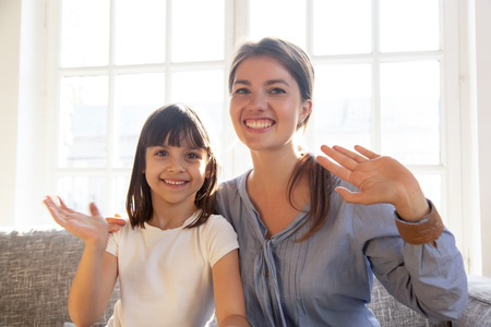 Pretty family happy mom little daughter looking at camera talking to webcam waving hands vloggers make video call recording new vlog, head shot portrait. Modern tech and online communications concept Stock Photo