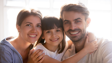 Positive family with pre-school beautiful daughter head shot portrait, pretty relative people sitting indoors feels happy smiling looking posing for camera. Concept of adoption child, care and love Standard-Bild
